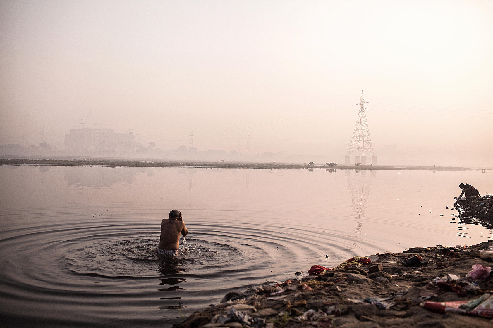 A Hindu devotee offers prayers after a dip in the Yamuna River